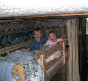 The kids playing in the upper bunk.